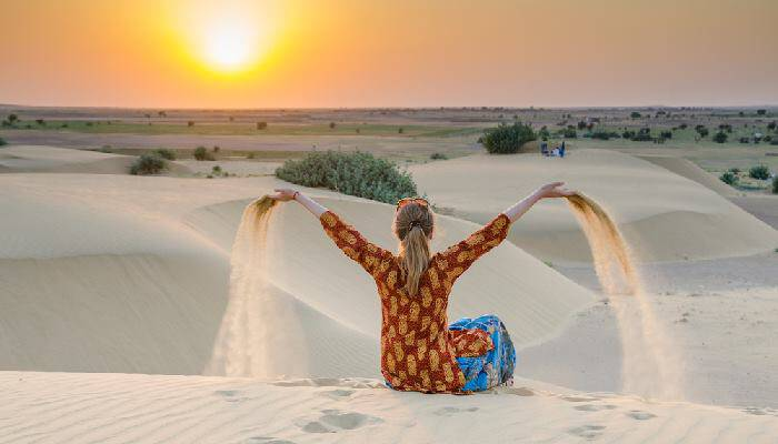 picture of a girl sitting in a desert in harem pants